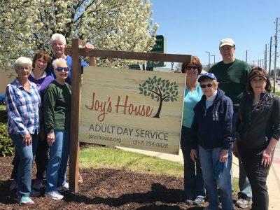 volunteers next to Joy's House sign