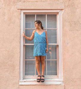 Model standing in window wearing dress